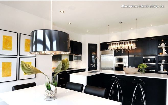 Sleek black kitchen design with yellow accents on the wall. Source: Houzz